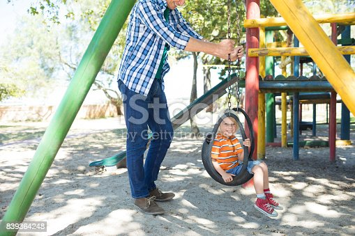 istock Low section of father pushing son sitting on swing 839364248