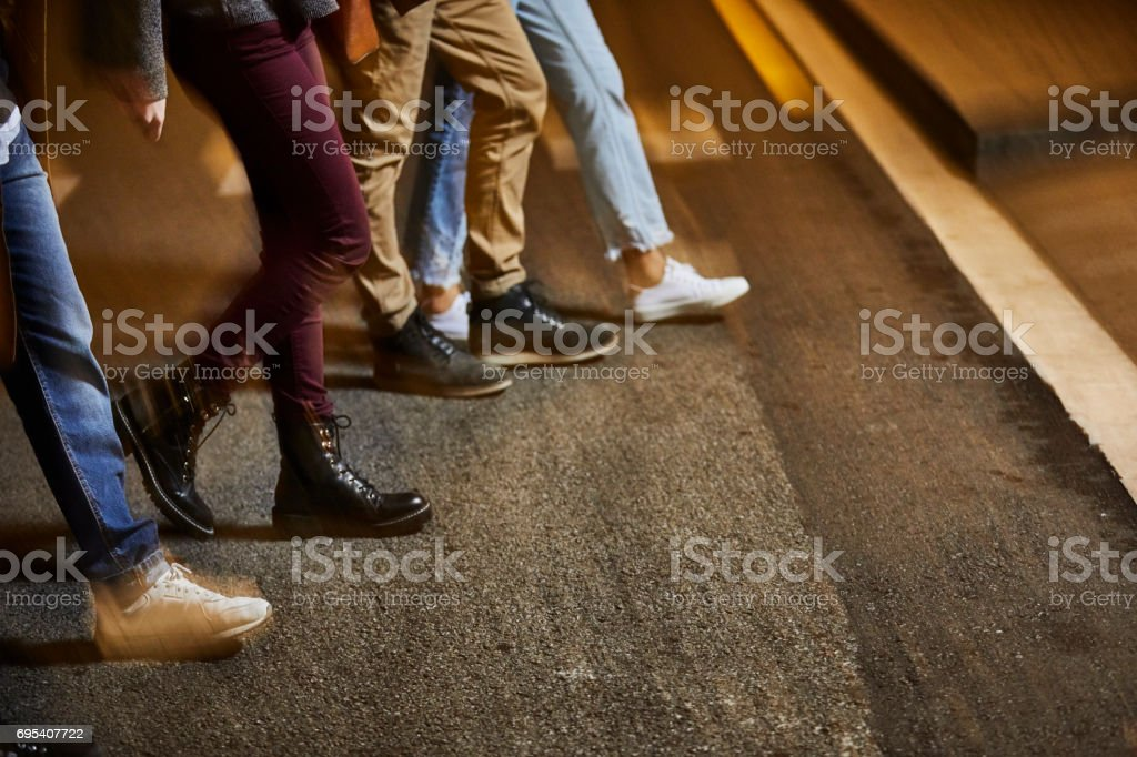 Low section of friends crossing street at night stock photo