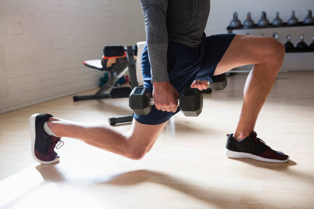 low section of male athlete exercising lunges in club - lunge stock photos and pictures