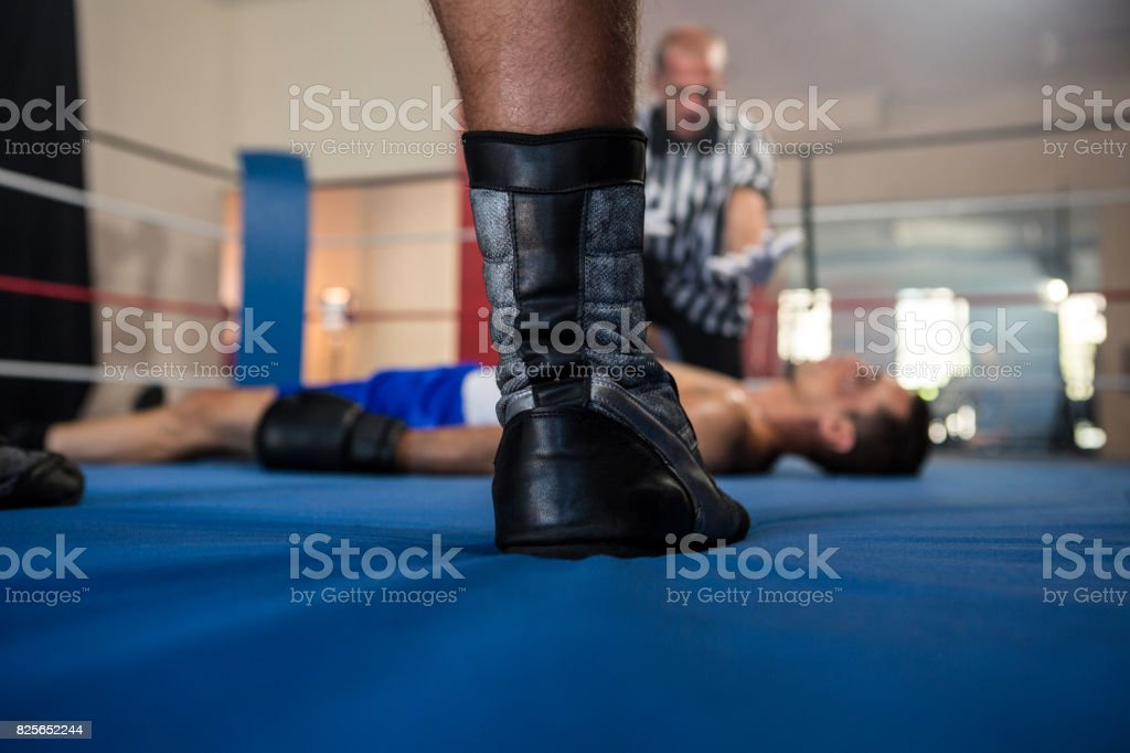 Low section of male boxer standing against referee by athlete stock photo