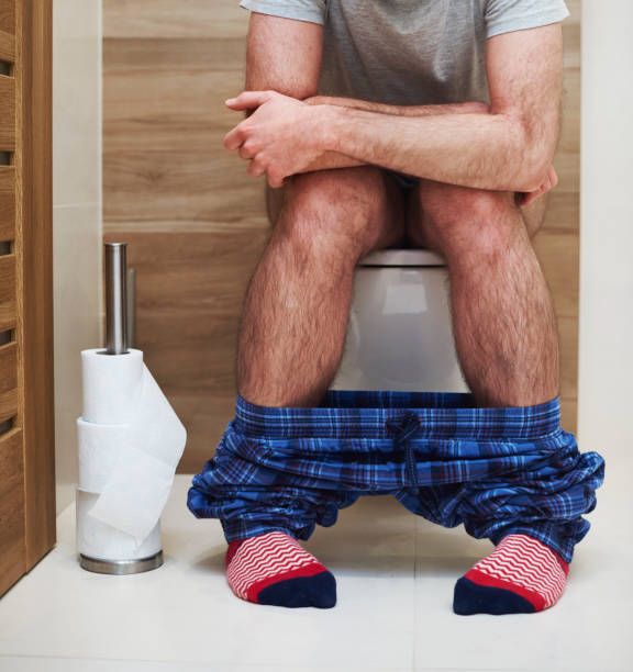 Low section of man defecating in the toilet stock photo