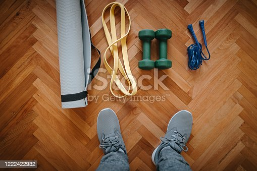Low section of man with exercise mat, dumbbell, jump rope and resistance band on hardwood floor