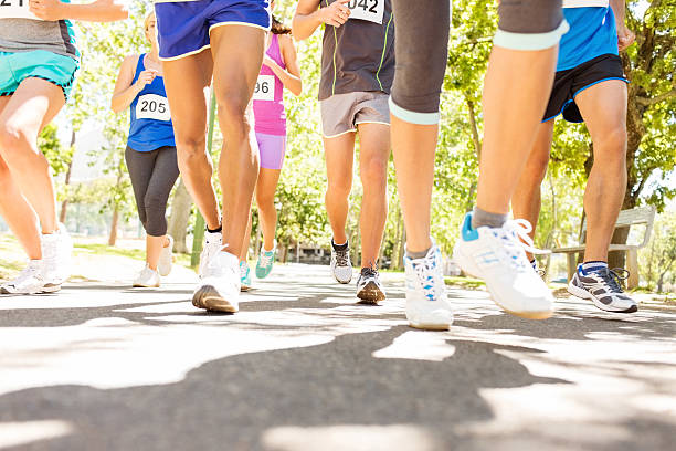 Low Section Of Marathon Runners Competing At Park stock photo