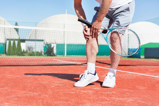 low section of mature man holding tennis racket while suffering from knee pain on red tennis court during summer - ginocchio foto e immagini stock