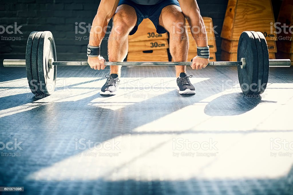 Low section of muscular man lifting barbell in gym Lizenzfreies stock-foto