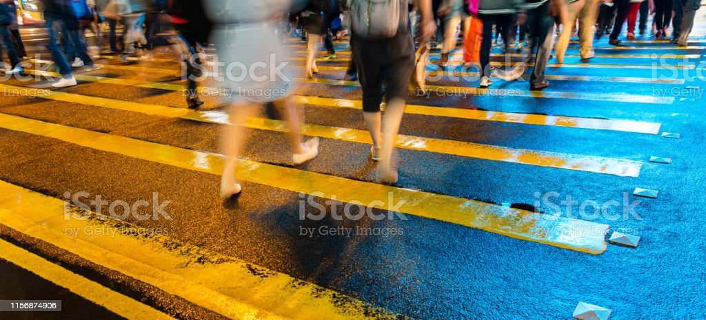 Low section of people crossing street in hong kong, motion blur.