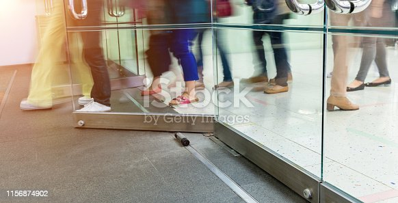 Low section of people walking through a glass door in a modern office building