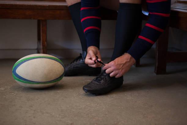 geringen teil der rugby-spieler, die schuhe zu binden - sitzbank schuhe stock-fotos und bilder