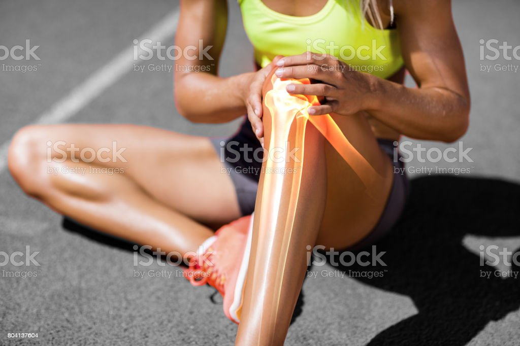 Low section of sportswoman suffering from knee pain stock photo