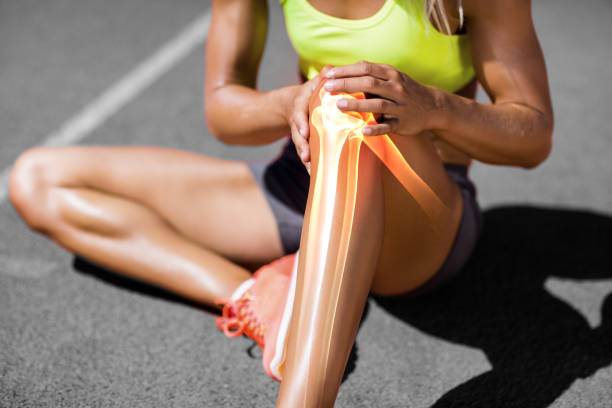 low section of sportswoman suffering from knee pain - human knee stock photos and pictures