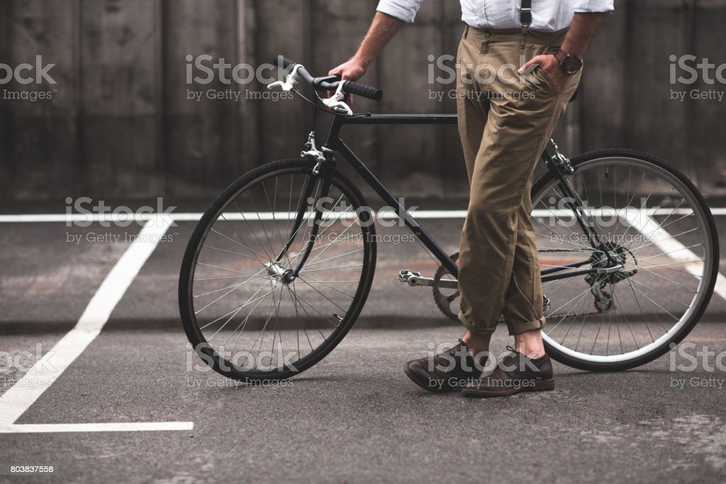 low section of stylish man in brown pants standing with bicycle - Royalty-free Adult Stock Photo