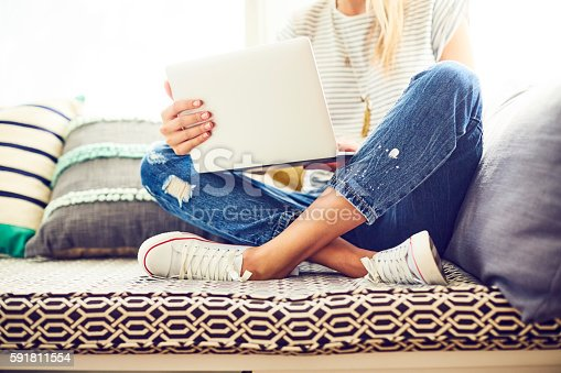 Low section of trendy woman using laptop. Female hipster is sitting with legs crossed on window seat. Woman is wearing blue jeans and canvas shoes at home.