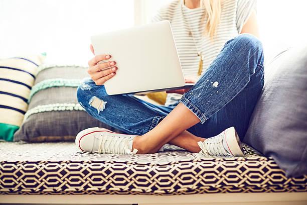 low section of trendy woman using laptop on window seat - branche partie photos et images de collection