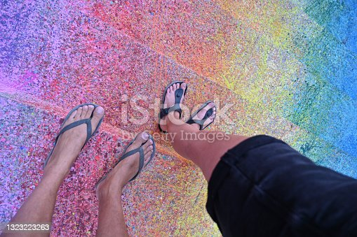 istock Low Section Of two persons  Walking On Colorful Street 1323223263