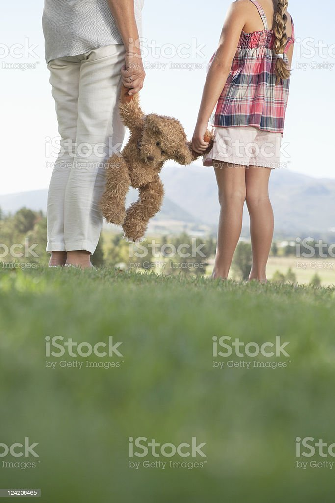 Low section of woman and grand daughter holding teddy bear in park royalty-free stock photo