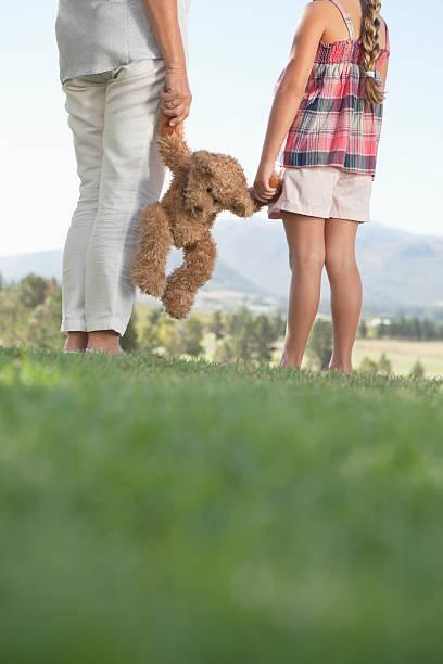 niedrige abschnitt frau und tochter holding teddybär grand - granny legs stock-fotos und bilder