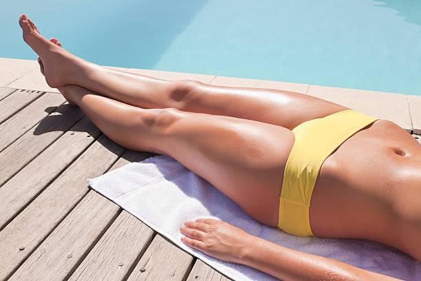 sezione bassa di donna supino vicino alla piscina - abbronzarsi foto e immagini stock