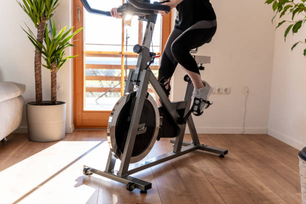 Low section of woman on exercise bike at home Low section view of a young woman in sportswear exercising on exercise bike at home exercise bike stock pictures, royalty-free photos & images