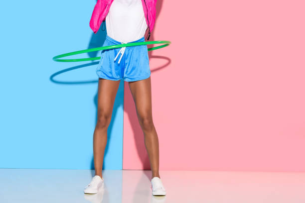 geringen teil frau posiert beim exersizing mit dem reifen - hula hoop workout stock-fotos und bilder