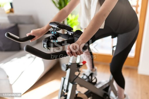 Low section shot of a woman in sportswear exercising on an exercise bike at home