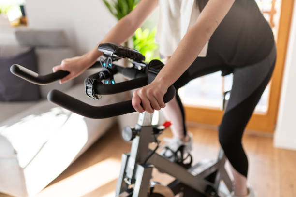 Low section of woman training on exercise bike at home Low section shot of a woman in sportswear exercising on an exercise bike at home exercise bike stock pictures, royalty-free photos & images