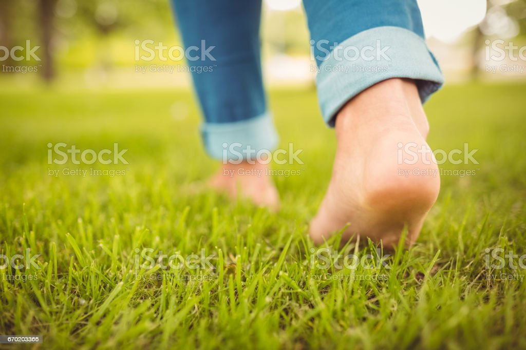 Low section of woman walking on grass stock photo