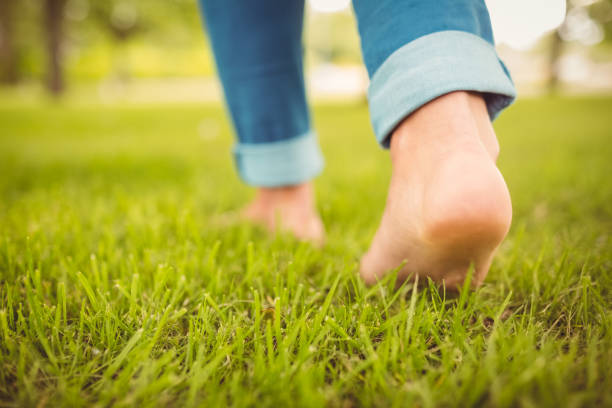 low section of woman walking on grass - scalzo foto e immagini stock