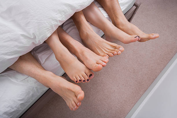 low section of woman with two men in bed - three people stock photos and pictures