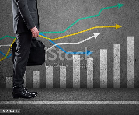 istock Low section view of a businessman standing with bar graph 623703110