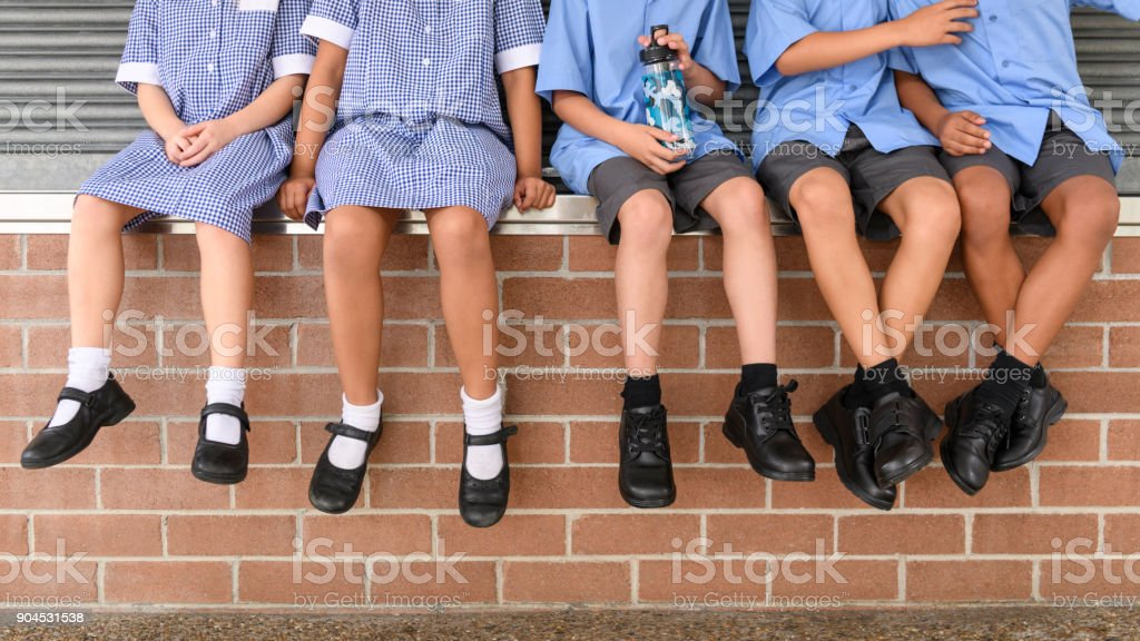Low section view of five school children sitting on brick wall wearing school uniform stock photo
