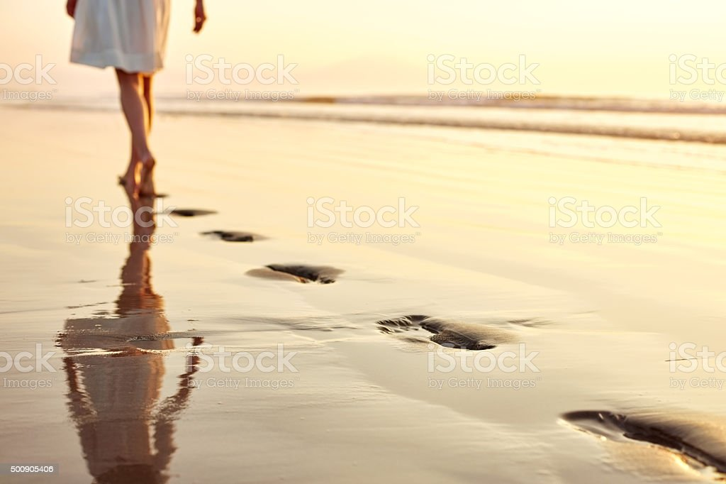 Low section woman leaving footprints while walking on wet beach stock photo