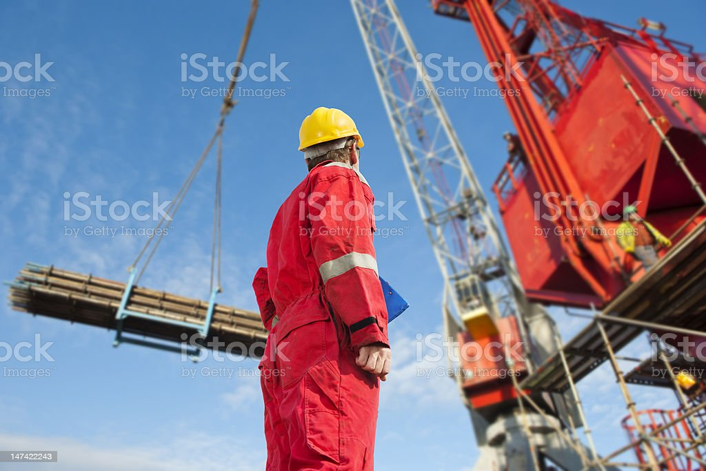 Low shot of a construction worker looking at a crane at work stock photo