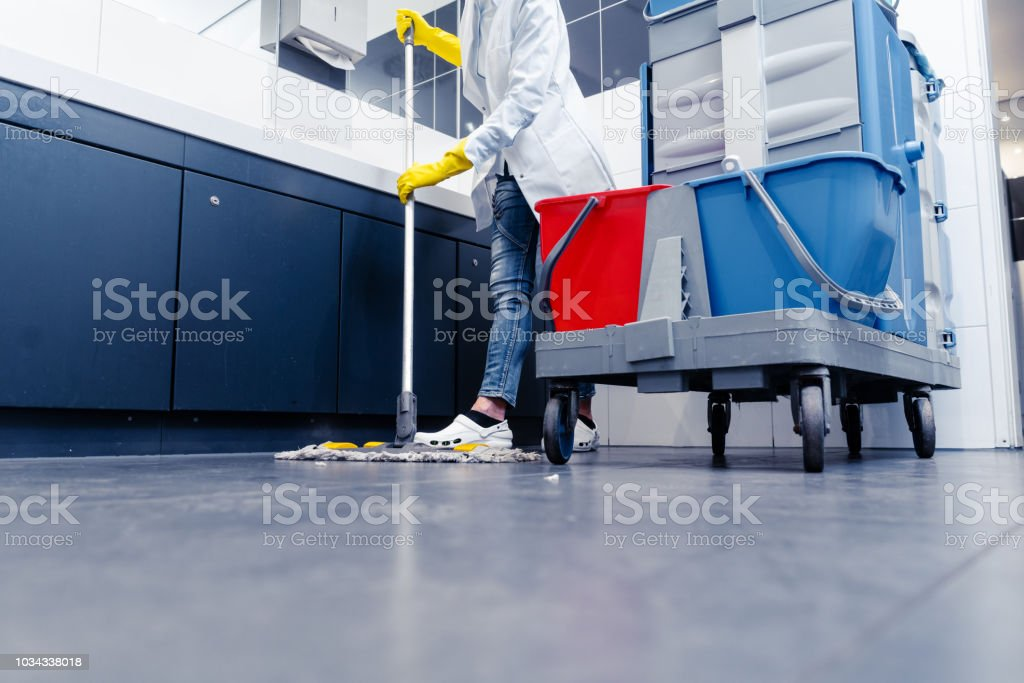 Low shot of cleaning lady mopping the floor in restroom stock photo