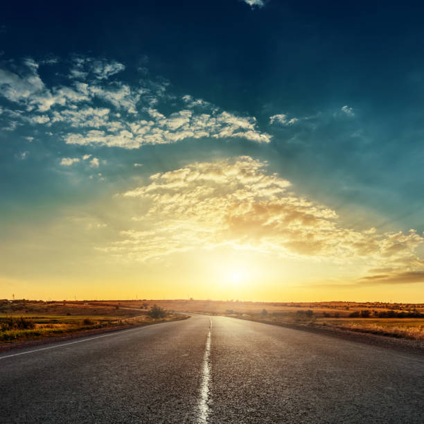 low sun in dramatic sky over asphalt road stock photo