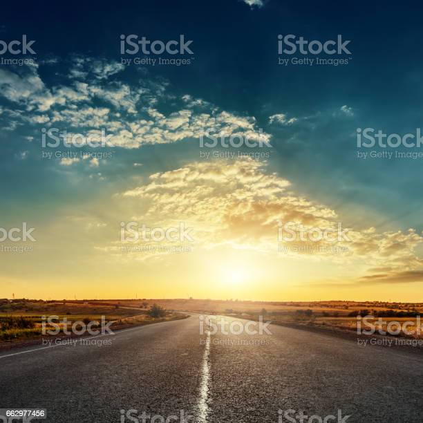 Photo of low sun in dramatic sky over asphalt road