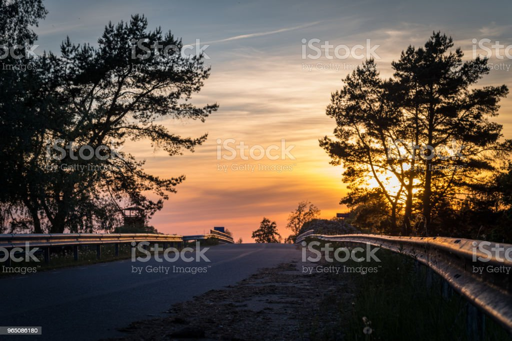 Low sun in dramatic sky over asphalt road royalty-free stock photo