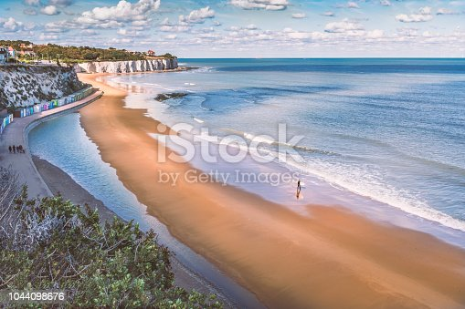 Low tide at Stone Bay, Broadstairs, Kent as summer turns to autumn, a lone surfer walks on the beach and a family on the promenade along side the beach huts and white cliffs.