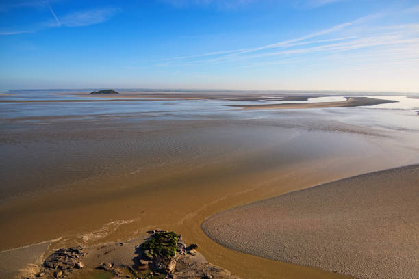 Low tide in front of Mont Saint-Michel abbey. Amazing landmark. Sunny spring morning view. Normandy, France, Europe Low tide in front of Mont Saint-Michel abbey. Amazing landmark. Sunny spring morning view. Normandy, France, Europe. manche stock pictures, royalty-free photos & images