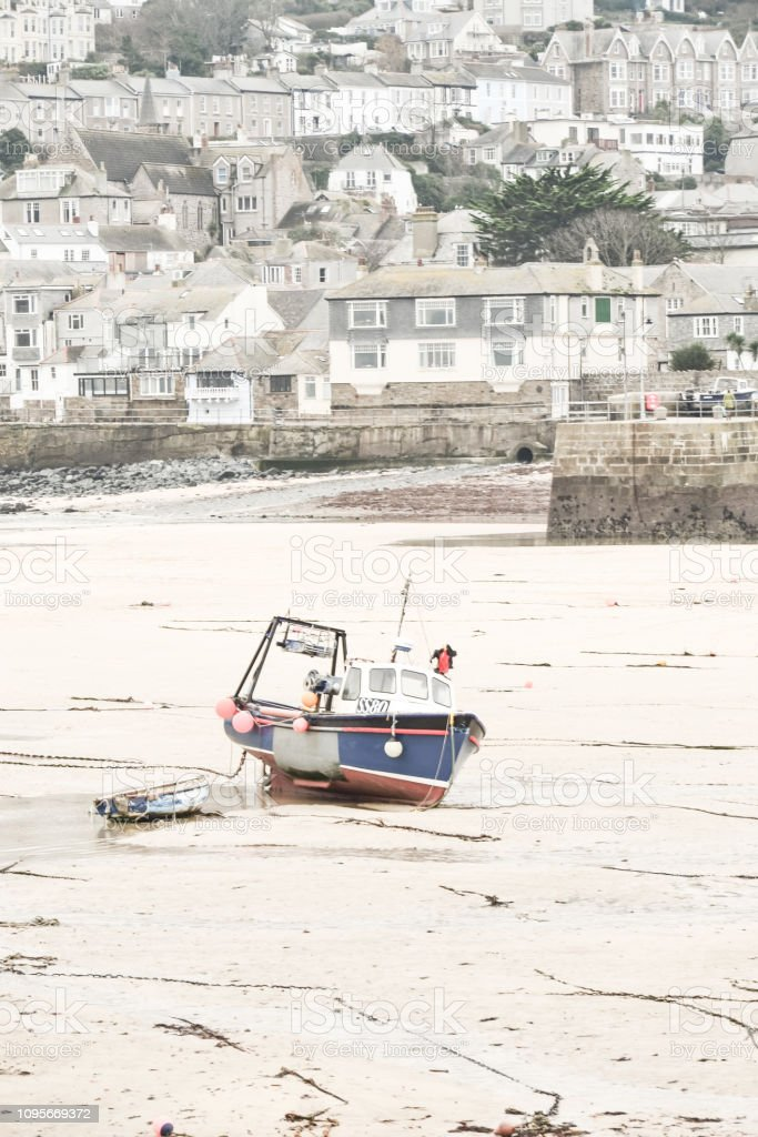 Low tide in the little protected harbour leaves the boats stranded on...