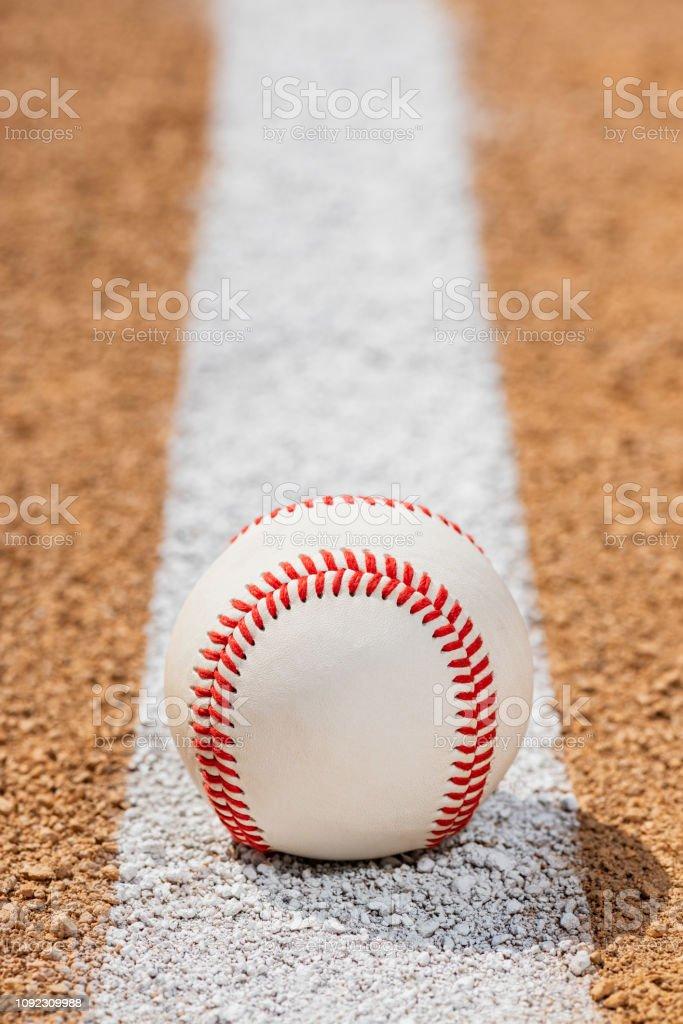 Low view of baseball on Foul Line on dirt of baseball diamond stock photo