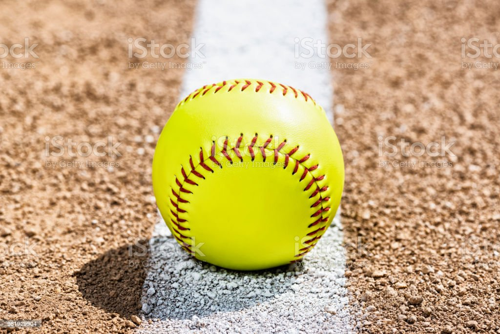 A low view of a yellow softball sitting on a painted white Foul Line...