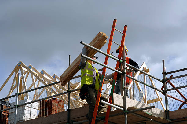 Low view of two construction workers on top of house frame A pair of roofers working on a construction site in Manchester, England. No sharpening in camera or pp. scaffolding stock pictures, royalty-free photos & images