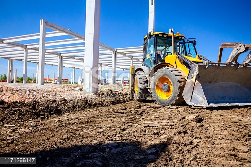 Excavator's front tool, bucket, blade, tall concrete pillars are behind at building site.