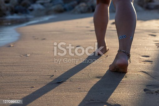 Low view point of a Thai woman bare feet walking on the beach at Atlantic ocean shoreline in Portugal. Woman strolling alone on the beach at sunset. Travel leisure concept. Backpacker idea.