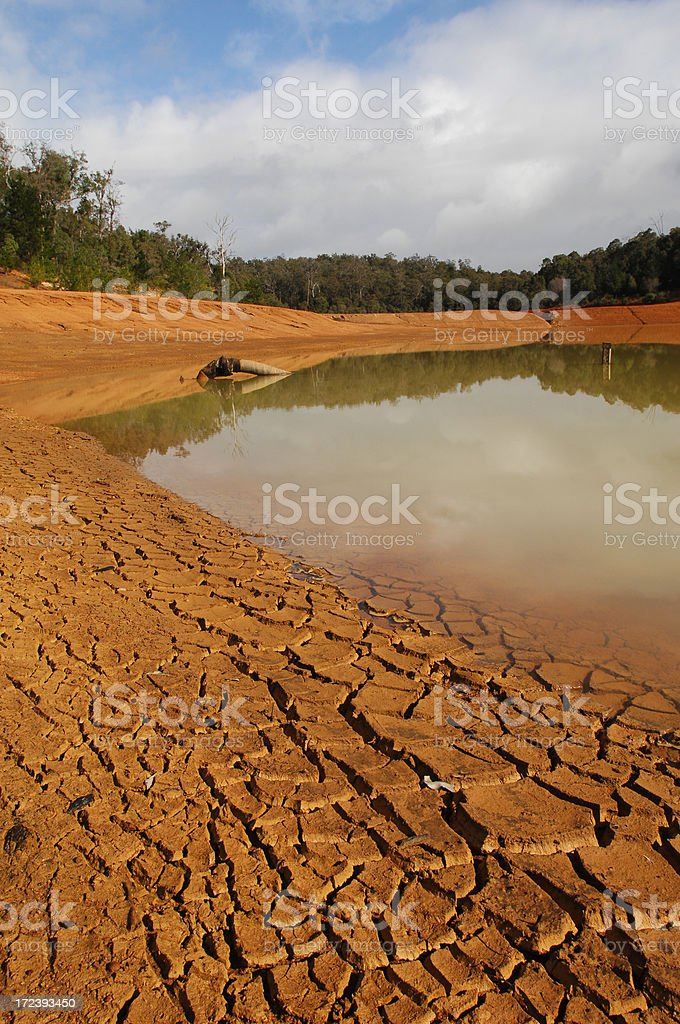 Low water in a dam showing exposed cracked mud flats. royalty-free stock photo