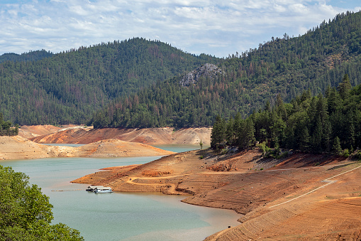 Low water level at Shasta Lake, California, USA due to multi-year drought. The lake is 100 feet/33 meters below full capacity. Paved boat ramp in lower right no longer reaches water. Dirt boat ramp provides temporary access. Houseboats moored near swimming platform who's underwater anchor, which should be vertically below platform, lies exposed horizontally on dry shore. Shasta Lake provides recreation as well as drinking water and irrigation water to locations as far away as Los Angeles 500 miles/800km away. June 21, 2021.