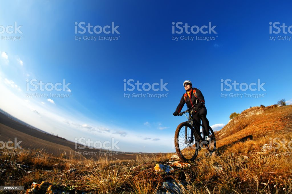 Low, wide angle portrait against blue sky of mountain biker going downhill. Cyclist in black sport equipment and helmet royalty-free stock photo