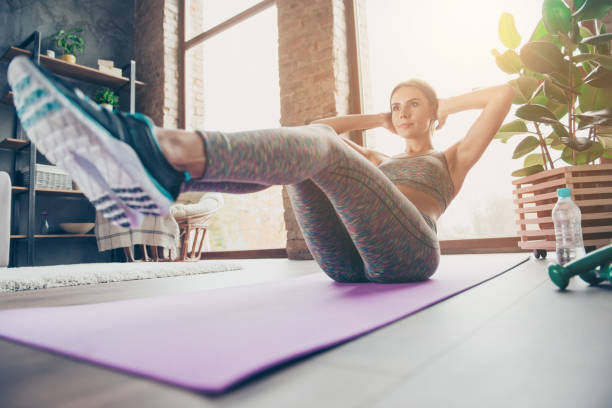 low-angle photo of attractive sportive pretty strong muscular flexible woman doing sit-ups and holding legs in air trying to keep balance in reflection, sun glare, beam, ray, sunny day - sit ups stock photos and pictures