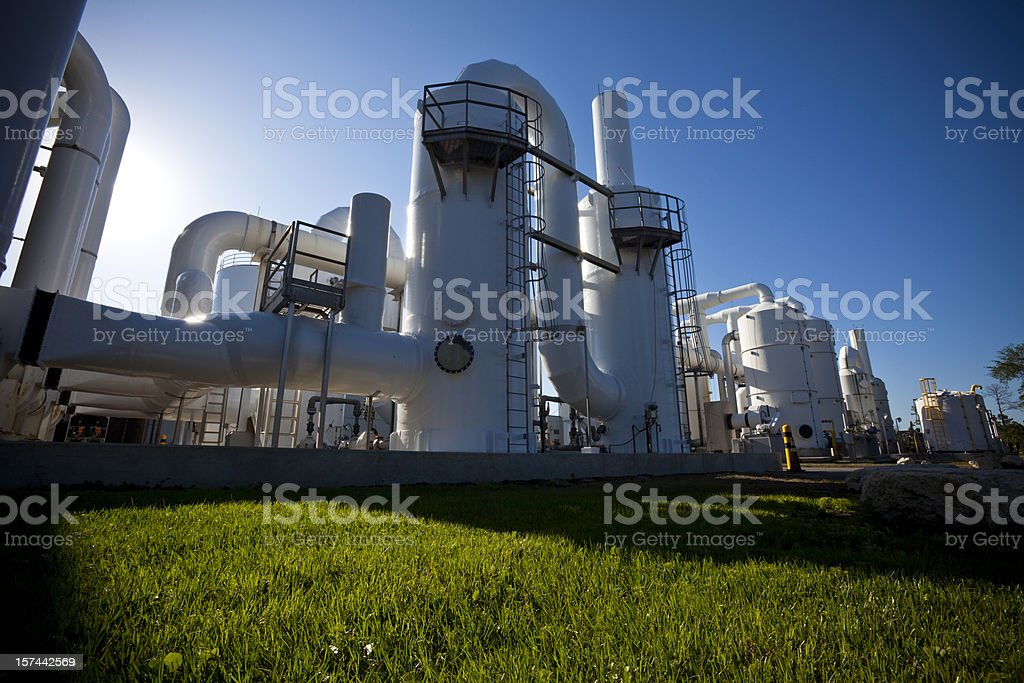 Low-angle shot of water purification plant, shadows on grass stock photo