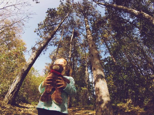 Niedrigwingenblick als kleines Mädchen im Wald mit Teddybär – Foto
